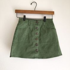 "NWT Brandy Melville Olive Green Nanna Skirt BRAND: Brandy Melville ITEM: Super cute denim skirt in an olive green color. Has two pockets, buttons down the front, and belt loops | NWT | NO FLAWS SIZE: 24"" (XS/0) Brandy Melville Skirts"
