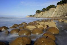 "Bowling Ball Beach in California - These bowling balls, technically called ""concretions,"" formed in layers of sedimentary rock, and millions of years of weathering have uncovered them."