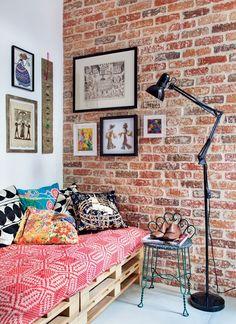 A cama de paletes foi feita sob medida para o quarto de hóspedes, mas o protagonista da decor desse ambiente é a parede de tijolinhos, que ficou uma graça com esses quadros pendurados.