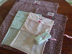 Kit de sacos multiuso em tecido de algodão: <br>- 3 Sacos com visor em plástico transparente (23 x 32cm); <br>- 2 Sacos modelo Roupa Limpa/Roupa Suja (Saco I: 30 x 38cm <br> e Saco II: 45 x 53cm). <br>Podem ser usados para roupas, sapatos, produtos de higiene e fraldas!! Chega de bagunça na mala ou na mochila da escola! Também são itens essenciais na mala da maternidade! Muito prático, não?! Os sacos são fechados com botão. Tecido pode estar indisponível.