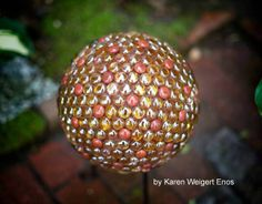 Decorative Garden Balls Ideas & Instructions: Garden art balls (spheres, globes) can be made from various repurposed items such as old bowling balls and glass lamp globes. You can cover a garden ball in anything that has a flat surface for adhesion and can withstand the weather - flat marbles/glass gems, coins, stones, aquarium pebbles, costume jewelry, etc. Or you could paint or decoupage it.