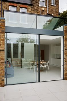 Minimal frame sliding doors with clerestory glazing and a frameless structurally glazed roof