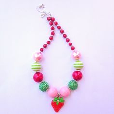 Red, pink, and green beads with a red strawberry pendant and small red pearl beads along the sides.