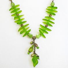 "Necklace made with green sea glass beads, pearls, and antiqued brass. This sea glass bead shape is called the ""fish bone""."