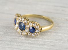This three stone antique Victorian ring is made in 18k yellow gold with three sapphires encircled by old european cut diamonds in a classic victorian setting. Circa 1880 A lovely alternative to a typical engagement ring or an everyday piece…. either way it's a stunner. Sits perfectly low on the finger.Learn more about Victorian rings Diamond and gold mining has caused devastation in areas such as Africa, wreaking havoc on delicate ecosystems and communities. Choosing to go vintage, you are…