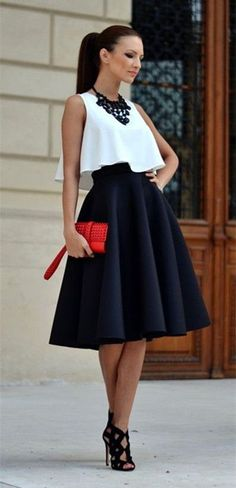 Black statement necklace, a flowy white crop top, a black skirt, black cutout heels, and a red clutch.