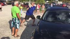 Un hombre rompe la ventana de un coche con una gran piedra para sacar a un perro del interior