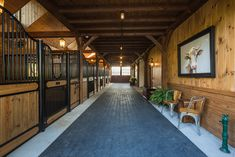 A spacious aisle with rubber pavers provides a safe and durable surface. Bank Barn, Barn Siding, Horse Barns, Carriage House, Stables, Surface, Horse Stables, Horse Stables, Horse Stalls