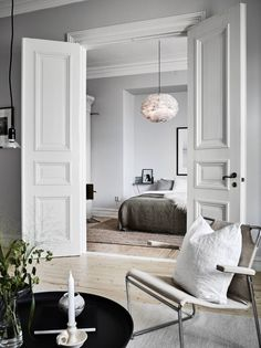 Classic elegance and Nordic minimalism paired in this living room and bedroom - - Classic elegance and Nordic minimalism paired in this living room and bedroom. Classic elegance and Nordic minimalism paired in this living room and bedroom. Home Bedroom Interior Barn Doors, Home Interior, Apartment Interior, Double Doors Interior, French Apartment, Apartment Door, Parisian Apartment, Dream Apartment, Apartment Design
