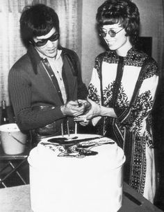 Bruce and Linda cutting a (Birthday? Anniversary? Movie wrap?) cake featuring a Bruce Lee flying kick in icing.