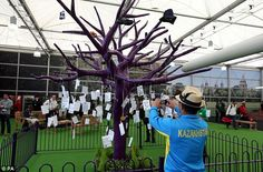 """Memories: A member of the Kazakhstan contingent takes a picture of a tree with """"Games Moments"""" hung on its branches.  Astroturf was also on the makeshift floor of the temporary Terminal at Heathrow airport!  .......Olympics 2012- London, England."""