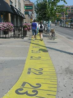 """Measuring North"" - photo by Steve Harris, via Flickr;  One half of a measuring tape painted along a sidewalk in the Fashion District in Toronto, Ontario, Canada"