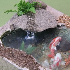 The realistic stream of water entering this dolls house scale koi pond is made from tar gel acrylic medium painted over the edge of a rock and allowed to drip onto the pool surface.