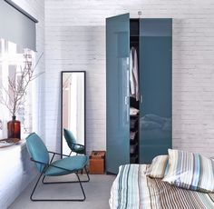 Use teal accents for effortless bedroom elegance, featuring PAX wardrobes, PALMLILJA bedding and a VILLSTAD chair.
