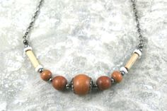 Light brown wood, bamboo, and shell necklace with gunmetal black accents and chain by Earthwear Collection