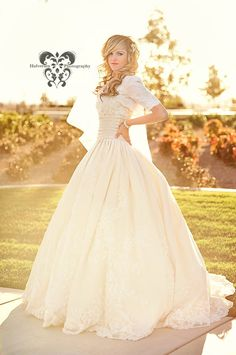 Gorgeous wedding dress - it's conservative, and fashionable! I love the ballgown skirt which appears to be lace appliques on a taffeta skirt. I like the midriff cummerbund nips the waist. The sleeves appear to be a bolero jacket.