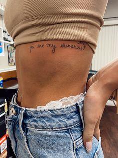 Rib Tattoos For Women Quotes, Girl Rib Tattoos, Rib Tattoo Quotes, Side Hip Tattoos, Small Rib Tattoos, Quote Tattoos Girls, Hip Tattoos Women, Dainty Tattoos, Tattoos On Ribs