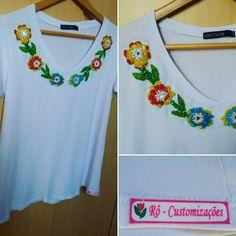 Camiseta branca customizada com bordado de flores colorida, fazendo a vez do maxi colar