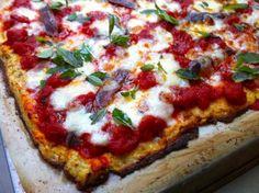 De wonderbaarlijke uitvinding van de bloemkoolpizzabodem   etenenzo 1 kilo bloemkool (gewicht zonder bladeren, maar inclusief stronk, die je dus ook gewoon kunt gebruiken) 50 g geraspte Parmezaanse kaas 2 bollen mozzarella 1 teentje knoflook, fijngesneden 1,5 tl gedroogde oregano 1 groot ei 1 portie tomatensaus 1 blikje ansjovisfilets olijfolie een handje basilicumblaadjes Nog een variant met info, NRC