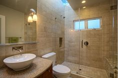Luxurious bathroom design with glass enclosed shower with gorgeous tiles.