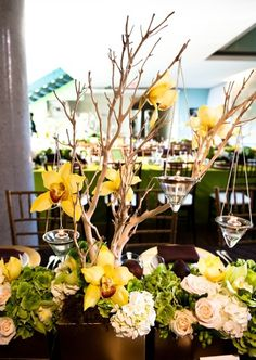Manzanita tree centerpieces with yellow orchids and candlelight.