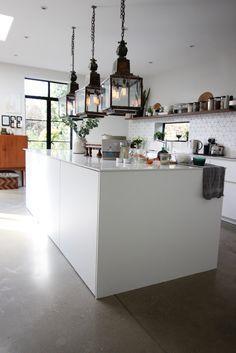 White kitchen with big island   grey concrete floors   large vintage copper lanterns   Friday favourites