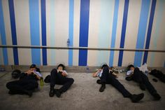 Police officers sleep as protesters (not pictured) block the main street to the financial Central district outside the government headquarters in Hong Kong, in this September 29, 2014 file photo.  REUTERS/Carlos Barria/Files
