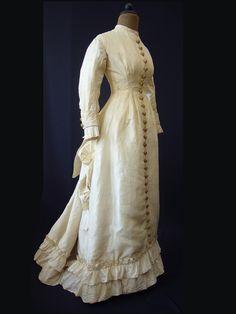 Wedding Dress 1875 - 1890 Description ... Taffeta dress, cream-colored, with trains, Cul de Paris, front buttoned throughout, long sleeves, Voulants Material / Technique ... Shell: silk taffeta, lining: cotton gauze, cotton fabric