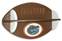 """Clemson Tigers Football Shelf by Fan Creations. $44.95. Officially Licensed Florida Gators Wooden Football Wall Shelf. 23 Inches Width x 12 Inches Height x 8 Inches Deep. Wooden. Carved 3D Logo. Unisex Adults. This unique shelf design can be used for decoration in a child's room, office, game room or even the bathroom. The perfect place to display trophies, photos, figurines, or other memorabilia. Team logo is carved in 3D. 23""""w x 12""""h x 8""""d"""