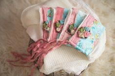 Couture Phantasies- Staci bonnet! Fun and colorful bonnet for infants.  Bright pinks, blues and greens with pink silk ties.  Removable embellishment on a clip, made of natural elements, hand crafted silk flowers