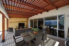 This cozy, enclosed patio is shaded by slatted wood roof, with dark wicker dining and living room style furniture sets next to floor to ceiling glass wall. Home, Wicker Dining Set, Enclosed Patio, Patio Room, Outdoor Decor, Modern Pergola Designs, Pergola Designs, Living Room Seating, Wooden Ceilings