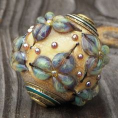 Focal bead with lots of golden aurae highlights and a little color showing from annodized aluminum beadcaps
