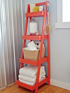 This bright orange ladder adds a pop of color and dimension in this contemporary white bathroom, and was built for storing toiletry items and towels in an unused corner of the room.