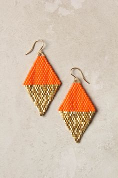 Send sartorial signals with these beaded tangerine triangles, reflected by glimmering gold. Handmade in Rwanda by Bluma Project, which supports women's employment in cooperatives throughout the world.