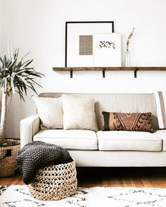 Simple and elegant natural modern boho living space. Tribal lumbar cushion. Textures linens and basket. Tall indoor plant.