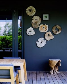 Patio space with wood slab slices hung on a blue wll