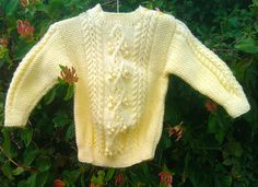 Child's handknit yellow aran sweater with shoulder opening.