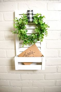 Now storing your mail can be so much CUTER! A white mail holder made with a wooden shutter and mini crate. At the top, a green eucalyptus wreath and a black & white gingham ribbon! Such a cute decorative mail holder with that farmhouse feel! Decor, Wreath Decor, Decorative Pieces, Entryway Inspiration, Farmhouse Wall Decor, Home Decor, Rustic Decor, Mini Crates, Crate Decor