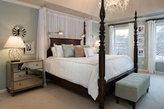 A traditional, mahogany four-poster bed adds drama to this serene bedroom. Romantic, glamorous elements, like the chandelier, mirrored nightstand and sheer curtains behind the bed, balance the dark wood bed frame.