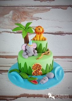 Cute Jungle Animal Cake. With fondant Lion, Elephant, Crocodile, Hippo and Snake . Additional pins for this cake... http://www.pinterest.com/pin/374784000213758504/ http://www.pinterest.com/pin/374784000213758477/ http://www.pinterest.com/pin/374784000213758441/