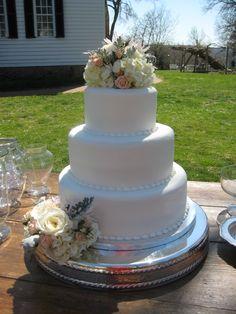Simple buttercream wedding cake with fresh flowers