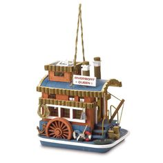 """This blue and brown birdhouse that looks like a steamboat is so darling. I love the little wheel on the side below the three windows and how there are two little flotation devices one blue and one red with an ax in front of them. The fact that it says """"Riverboat Queen"""" makes it perfect for a little family of birds. I love birds and boats, so maybe I should find something like this to add to my garden."""