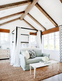 Bedroom with white walls, wooden ceiling beams, light green couch, patterned throw pillows, white coffee table, light brown rug, wood floors, white bedding, black bed frame, and beige bedside tables