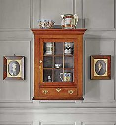 """The Pennsylvania Chippendale cherrywood hanging wall cabinet, circa 1790, was purchased at Sotheby's in 2002 from the Gunston Hall Plantation collection. Within and on top of the cabinet is part of the couple's collection of mocha ware. One of a pair of portraits by """"Mr. Boyd"""" flank the cabinet."""