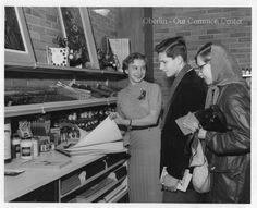 """ID#0207 Date: 1956-1960. This is a photo of customers in the Oberlin Consumer's Cooperative bookstore when it was located at # 55 East College Street. The Co-op moved into this building (currently the Slow Train Cafe) in 1956. Participant: Liz Burgess. Additional Sources: Oberlin Heritage Center: Fred Maddock files; McQueen, Albert, """"A Brief History of the Oberlin Consumers Cooperative and its Businesses.""""; Inge, Angela. """"A long Co-op History"""" Chronicle-Telgram, June 18, 2000."""