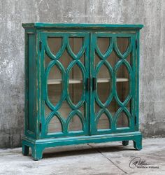 Built and carved in solid mahogany, with hand painted and a distressed finish in vibrant seaside azure blue, accented by aged white undertones, this Theona Console Cabinet is a coastal perfect storage piece for any small space in your coastal home.