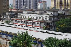 LRT station with train passing and old rotten developing in Kuala Lumpur, Malaysia - http://malaysiamegatravel.com/lrt-station-with-train-passing-and-old-rotten-developing-in-kuala-lumpur-malaysia/