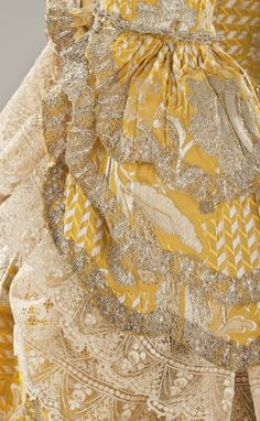 Detail sleeve, robe à la Francaise, England, c. 1760. Yellow silk plain weave with weft-float patterning and silk with metallic-thread supplementary-weft patterning, and metallic lace. #rococco return