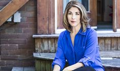 Naomi Klein sitting on the wooden steps of her Toronto home