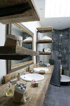 Du béton ciré gris anthracite sur les murs de la douche, du bois pour les étagères, le miroir etr le plan vasque
